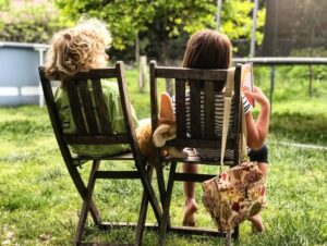 2 child sitting in a rocking chair